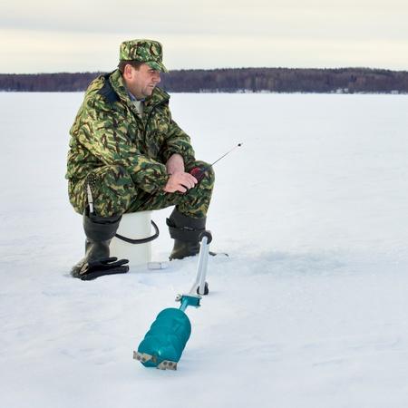 man fishing on the lake at winter photo