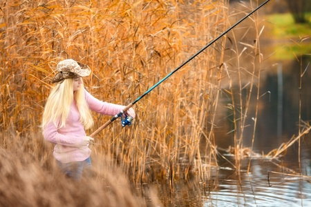 beautiful blond girl in pink sweater fishing photo