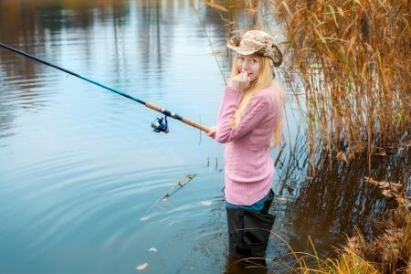 fisherwoman: beautiful blond girl in pink sweater fishing