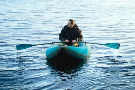 rowboat: fisherman in rubber boat on a lake