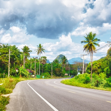 asphalt highway in jungle wit mount, Krabi, Thailand photo