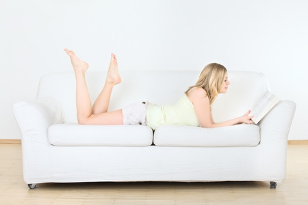 cute young girl reading on couch at home Stock Photo - 13194625