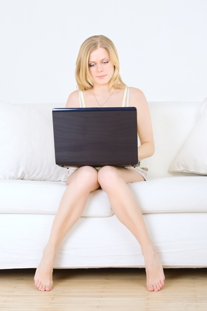 charming woman sitting on sofa with laptop photo