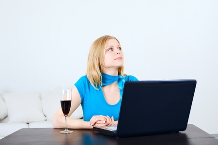 charming woman sitting at the table with laptop photo
