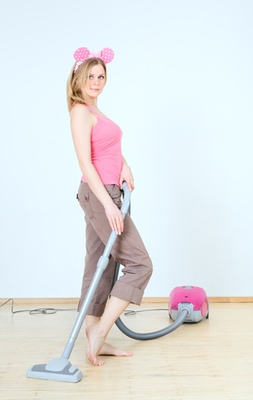 vac: cute young woman with vacuum cleaner at homework