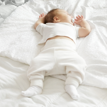 baby facial expressions: cute sleeping baby boy lying on the bed Stock Photo