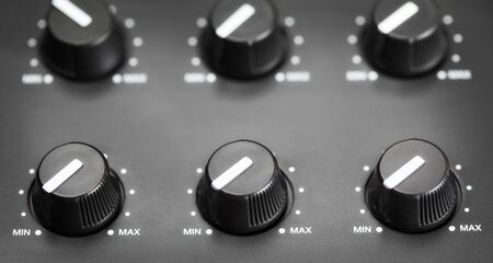 volume knobs with calibration on plastic plate, closeup photo