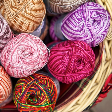 fleece fabric: balls of knitted wool in basket, closeup Stock Photo