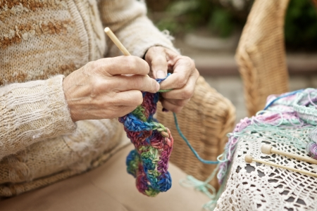 handicrafts: hands of old woman knitting wool, close up
