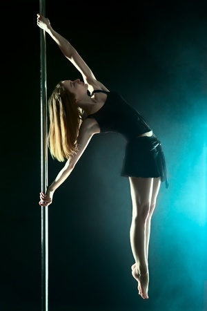 young sexy pole dance woman, dark background photo