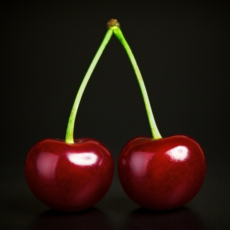 two fresh ruby cherries on black background photo