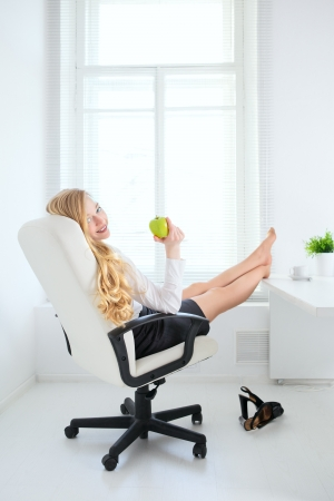 office break: happy office girl eating apple at break Stock Photo
