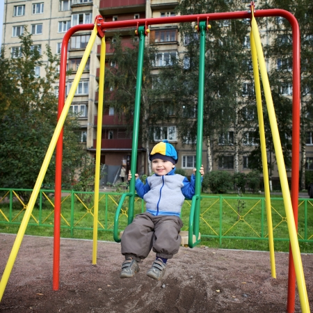 little boy teeter on playground at autumn photo