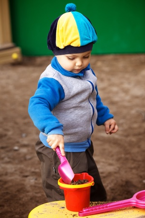 little boy playing in the sandbox at autumn photo