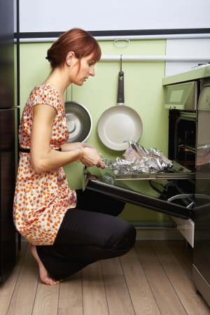 young woman cooking in oven at kitchen photo