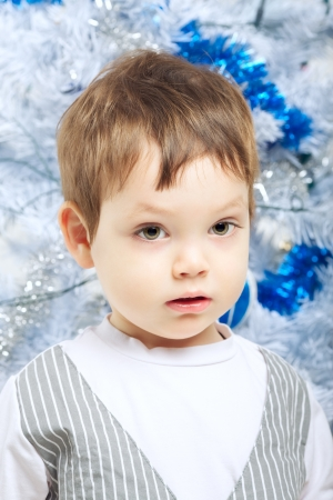 beautiful serious boy near christmas tree, portrait photo
