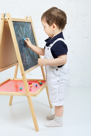 little boy drawing with chalk at blackboard Stock Photo