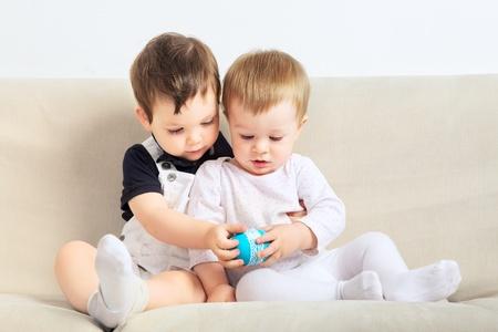 Zwei kleine Jungs auf der Couch sitzen und spielen Standard-Bild - 17408203