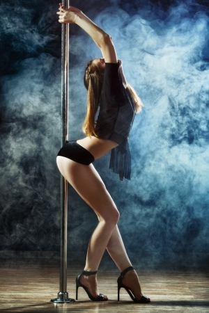 young sexy pole dance woman, dark background Stock Photo
