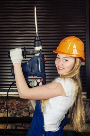 beautiful blond woman with heavy drill in his hand photo