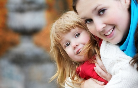 beautiful little girl and mother in autumn park