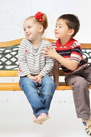frienship: beautiful girl and boy sitting on bench