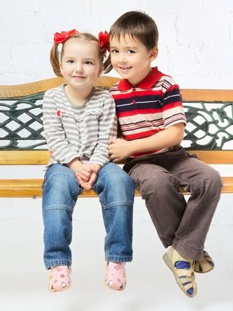 beautiful girl and boy sitting on bench photo