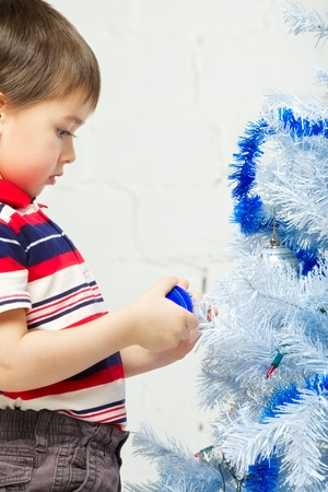 beautiful happy small kid decorate christmas tree photo