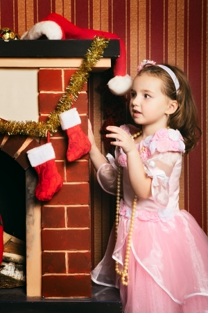 beautiful girl near fireplace looking for gifts Stock Photo - 17538377