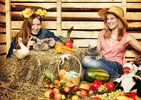hayloft: two girl with rabbit, cat and harvest on hayloft at summer day Stock Photo