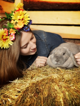 beautiful girl with rabbit on hayloft at summer day photo