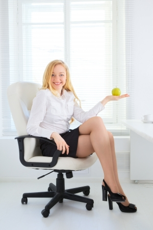 happy office girl eating apple at break photo