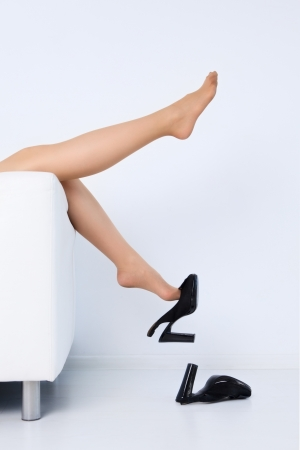 woman lying on sofa taking off high heel shoes