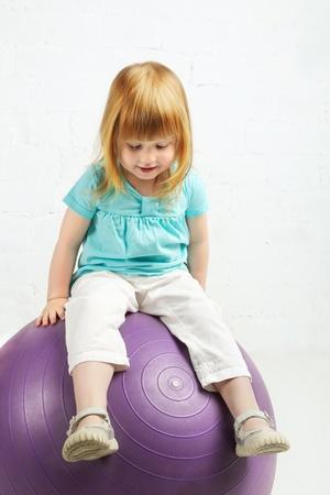 beautiful little girl sitting on big ball Stock Photo - 19516136
