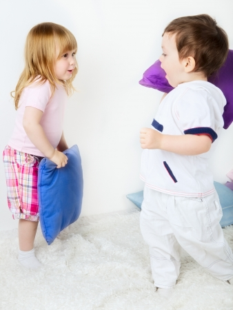 little boy and girl playing with pillows on bed photo