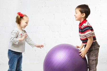 beautiful girl and boy playing with big ball photo