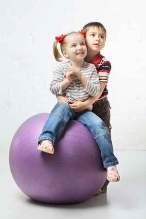 beautiful girl and boy playing with big ball photo