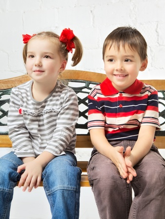 beautiful girl and boy sitting on bench photo