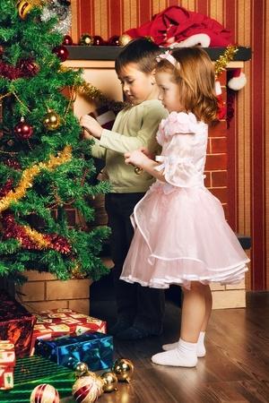 camino natale: bel ragazzo e ragazza decorare l'albero di Natale