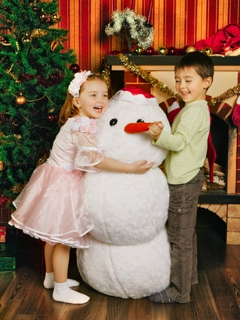 two beautiful child and toy snowman near christmas tree photo