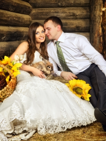 hayloft: charming bride and groom in hayloft with rabbit