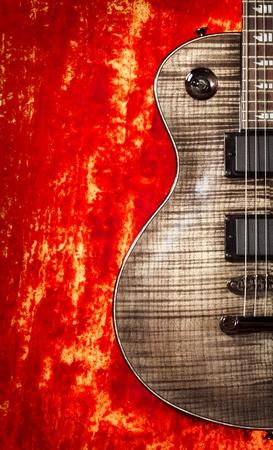 black electric guitar on red velvet background photo