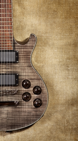 black electric guitar on brown canvas background photo