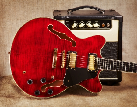 red semi-hollow electric guitar and amplifier on brown canvas background Archivio Fotografico