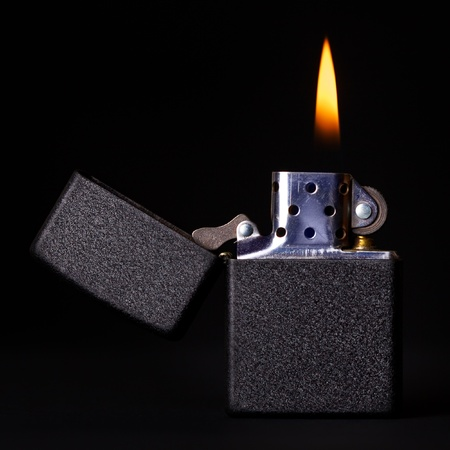 black gasoline lighter with flame on dark background photo