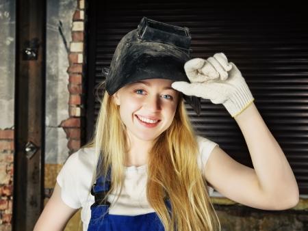 beautiful smiling blond woman in welder helmet
