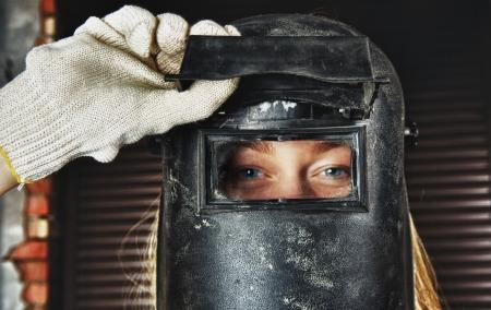 blond woman in overall and welder helmet