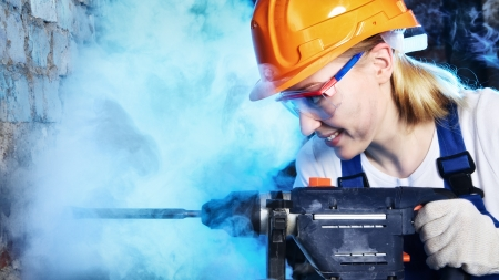 beautiful blond worker woman drill the wall