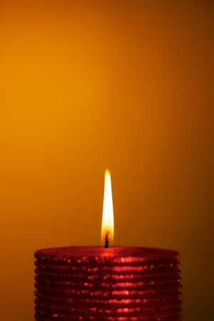 christmas spirit: burning wax candle on a yellow background