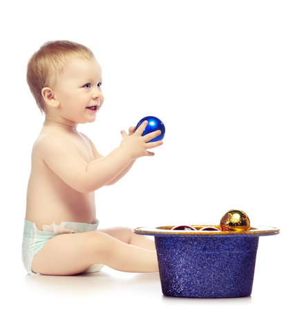 nappy new year: baby playing with christmas balls, isolated on white